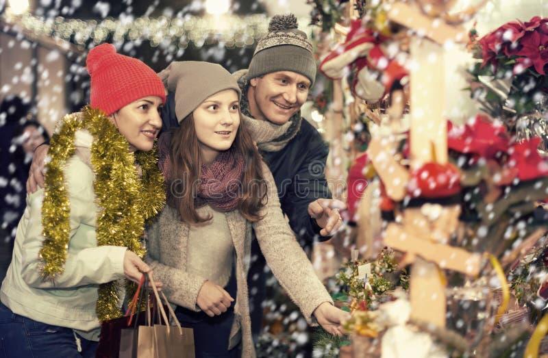 Familia de tres con el adolescente que elige decoraciones florales imagen de archivo
