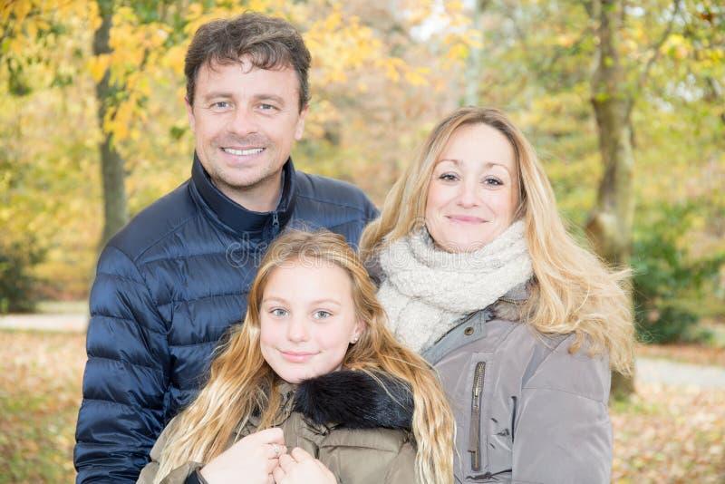 Familia de tres con la pareja y la hija rubia en otoño foto de archivo
