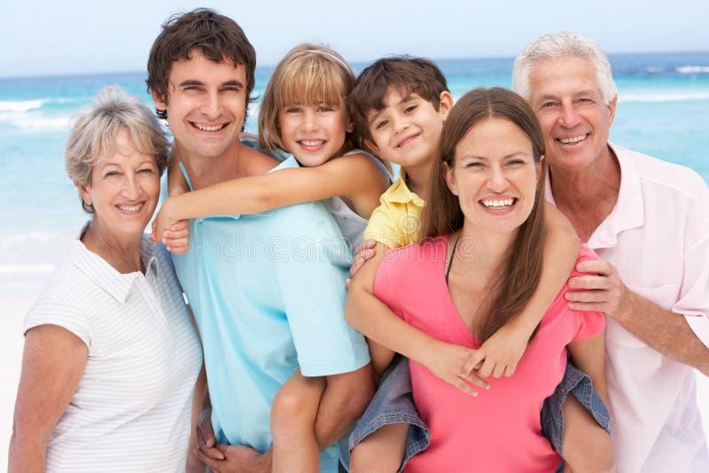 Familia de tres generaciones que se relaja en la playa imágenes de archivo libres de regalías