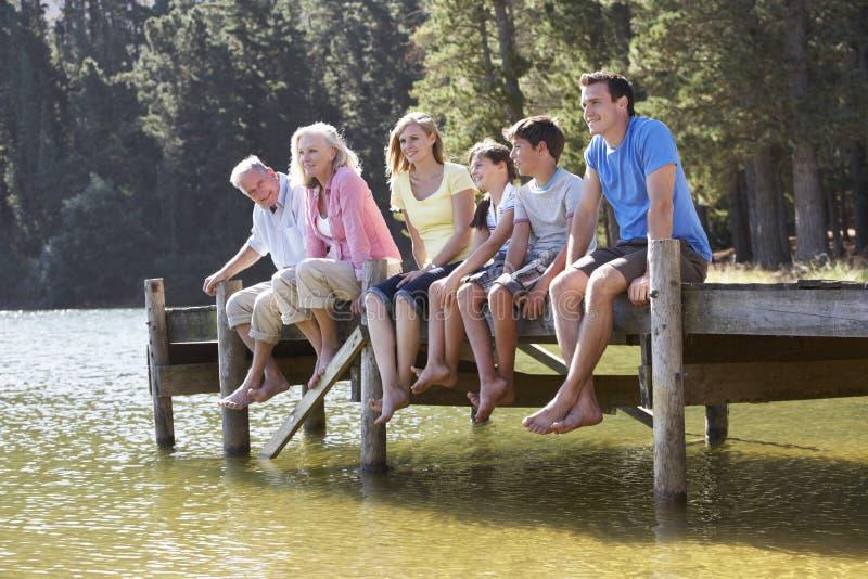 Familia de tres generaciones que se sienta en el embarcadero de madera que mira hacia fuera encima imagen de archivo