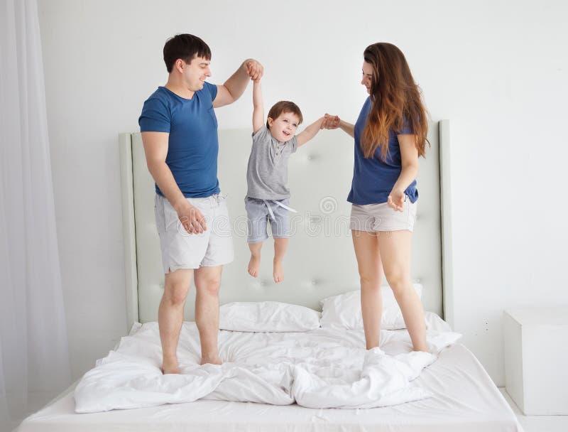 Familia de tres, padres jovenes y pequeño un hijo que salta y que se divierte en cama imagen de archivo libre de regalías