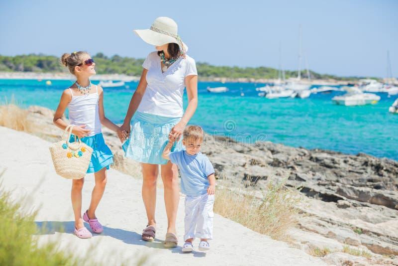 Familia de tres que recorre a lo largo de la playa tropical imagen de archivo