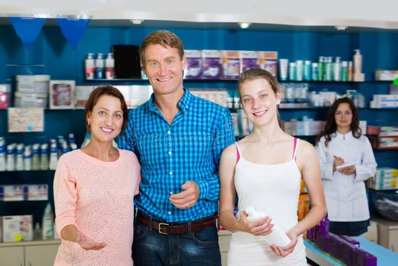 Familia de tres que se colocan en farmacia imágenes de archivo libres de regalías