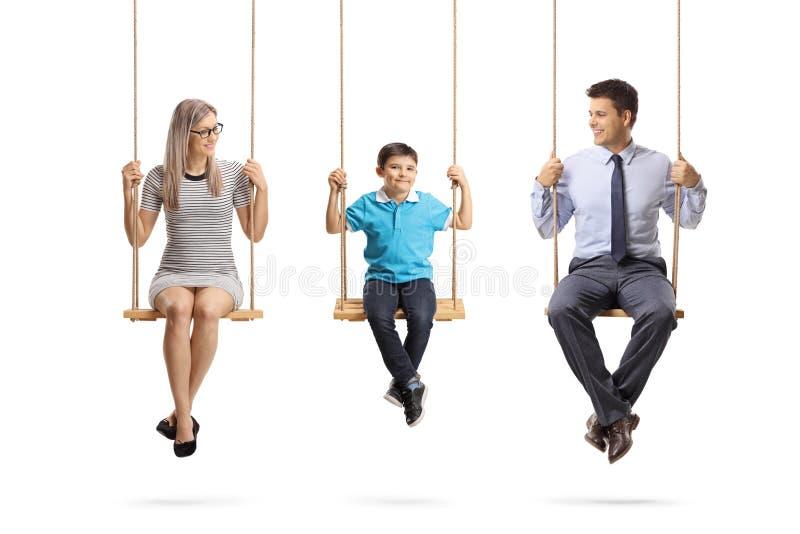 Familia de una madre, de un padre y de un hijo sentándose en oscilaciones imagenes de archivo