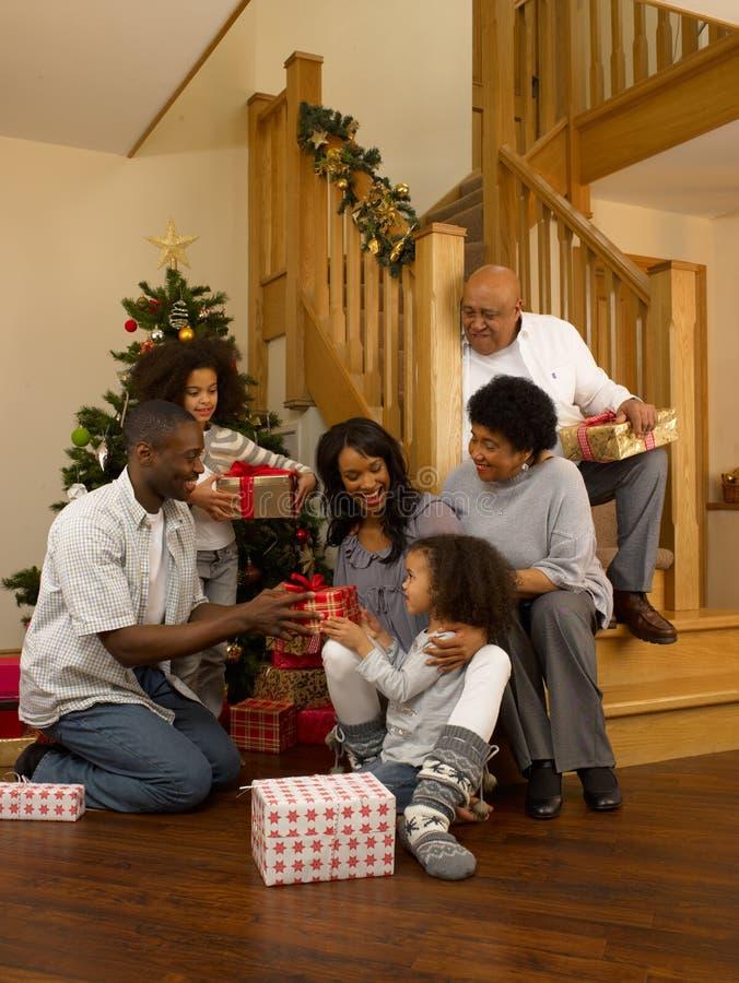 Familia del afroamericano que intercambia los regalos de la Navidad imagen de archivo libre de regalías