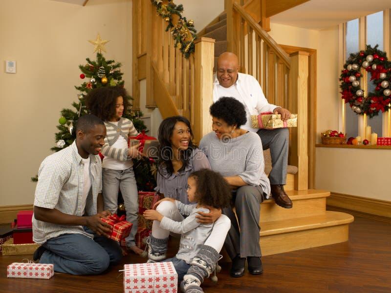 Familia del afroamericano que intercambia los regalos de la Navidad foto de archivo