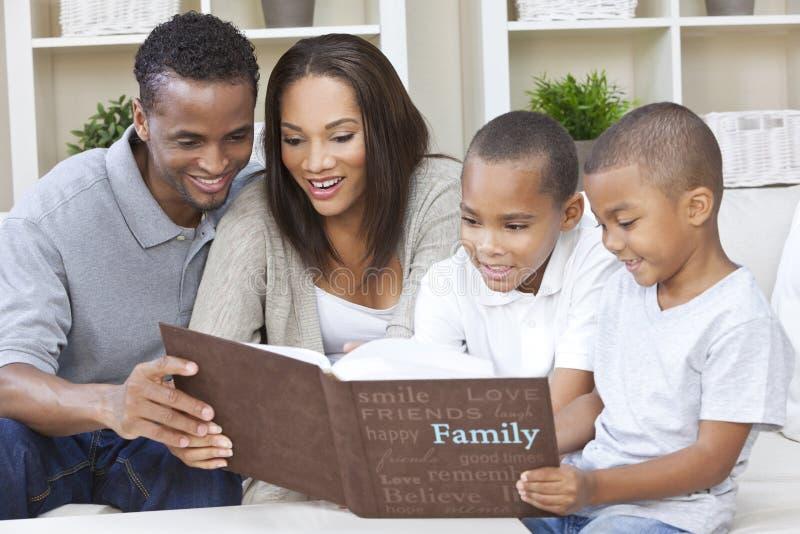 Familia del afroamericano que mira el álbum de foto fotografía de archivo libre de regalías