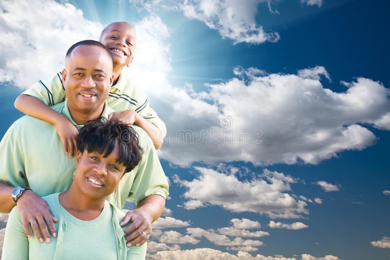 Familia del afroamericano sobre el cielo azul y las nubes