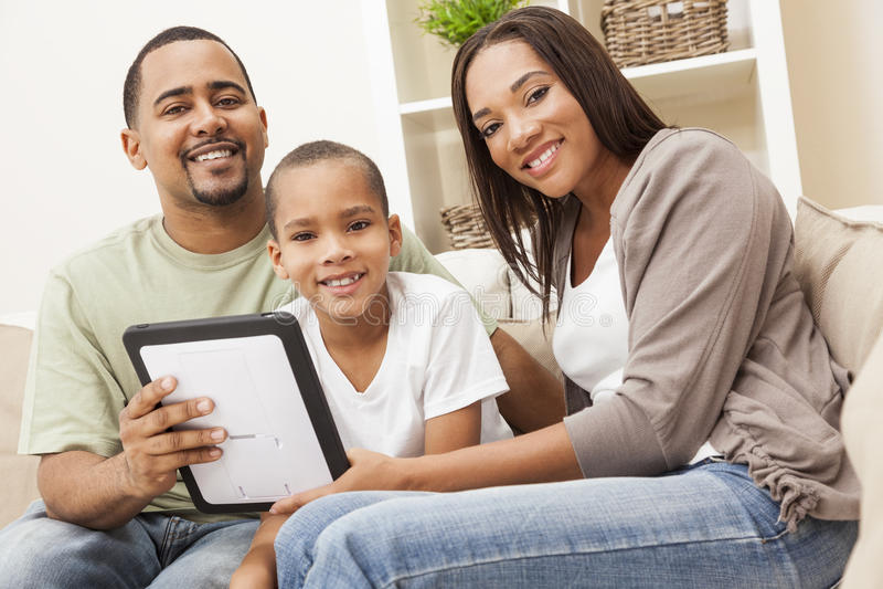 Familia del afroamericano usando el ordenador de la tablilla fotos de archivo