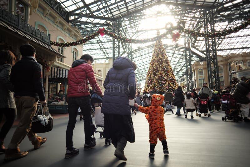 Familia del día de fiesta en el parque temático con los árboles de navidad en invierno En diciembre de 2017 fotos de archivo