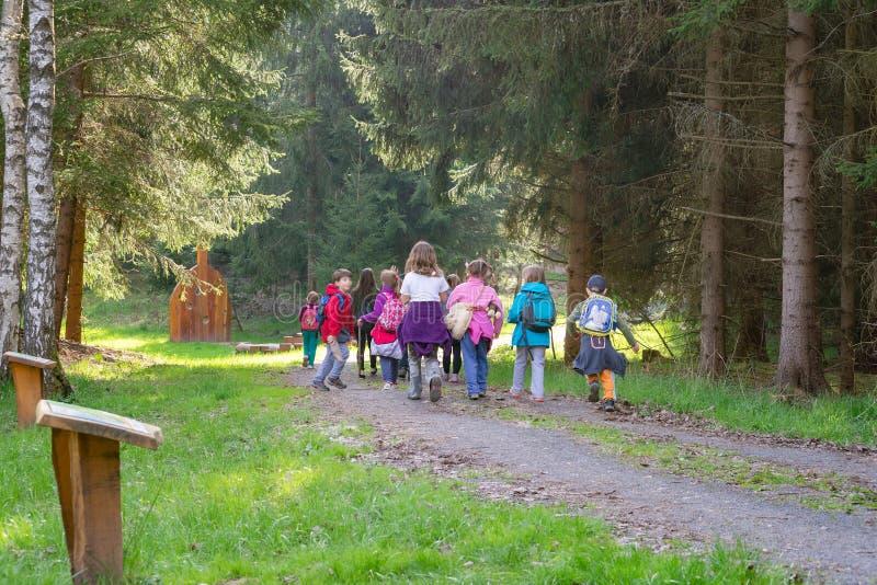 Familia del grupo de los alumnos de la guardería en bosque foto de archivo libre de regalías