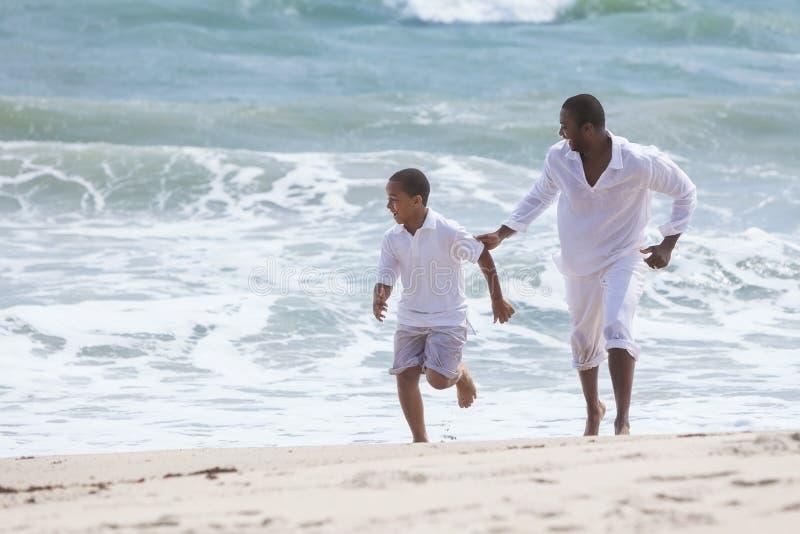 Familia del hijo del padre del afroamericano en la playa fotografía de archivo