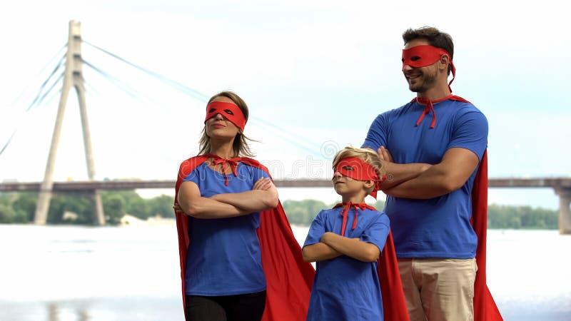 Familia del super héroe que se coloca audaz, trabajo en equipo, solución común de dificultades imágenes de archivo libres de regalías