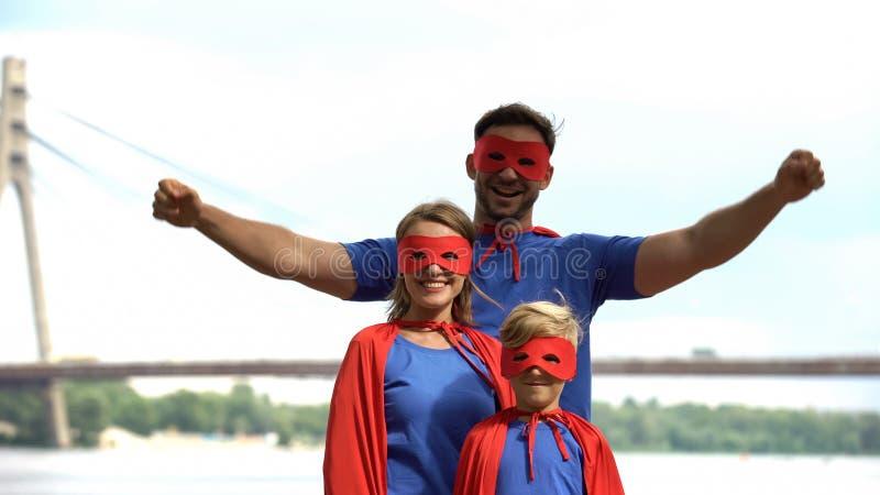 Familia del super héroe que tiene aire libre de la diversión, centro de entretenimiento, partido del b-día del traje imagen de archivo libre de regalías