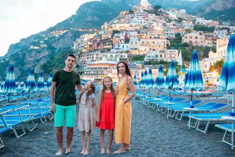 Familia delante de Positano en la costa de Amalfi en Italia en puesta del sol imagenes de archivo