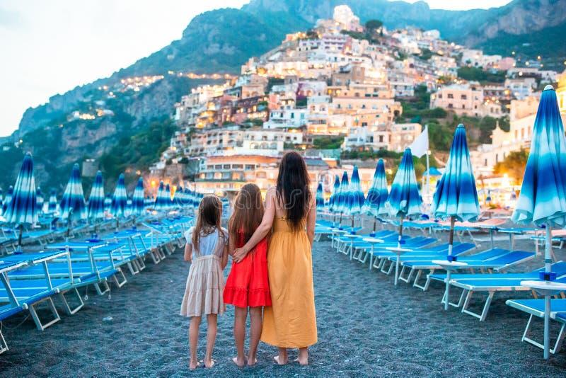 Familia delante de Positano en la costa de Amalfi en Italia en puesta del sol fotografía de archivo
