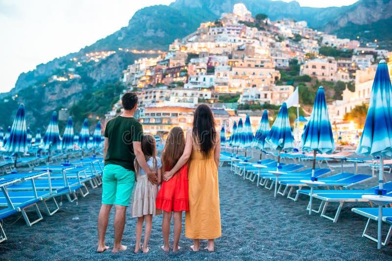 Familia delante de Positano en la costa de Amalfi en Italia en puesta del sol fotos de archivo