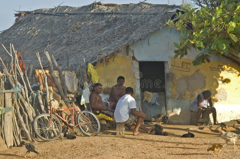 Familia delante de una casa típica de la arcilla imagen de archivo