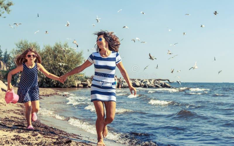 Familia despreocupada feliz que corre en la playa en el mar fotografía de archivo