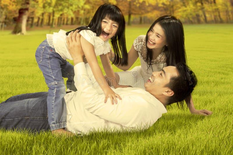 Familia despreocupada que juega en el parque del otoño foto de archivo libre de regalías