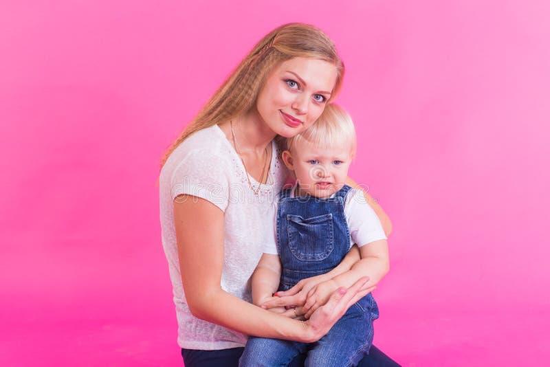 Familia divertida en fondo rosado Madre y su muchacha de la hija La mamá y el niño se están divirtiendo fotos de archivo