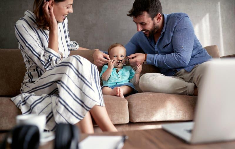 Familia divertida feliz con el bebé que juega con los vidrios fotografía de archivo libre de regalías