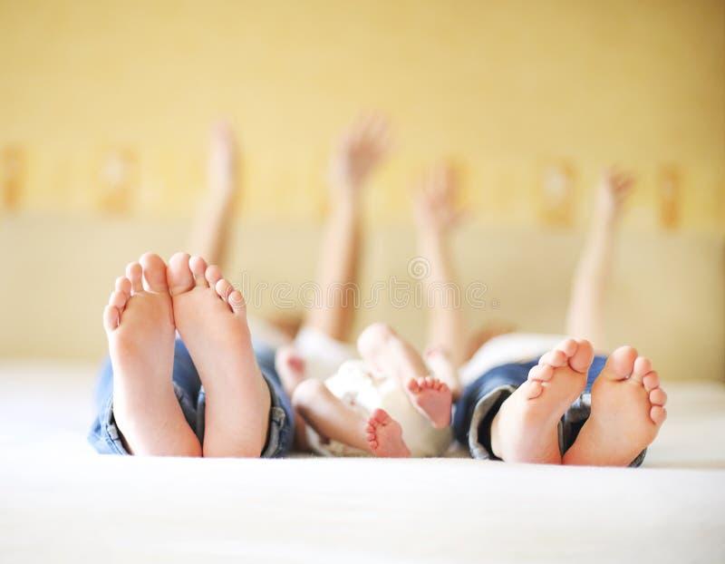 Familia dulce en cama Tres hermanas, cierre para arriba en pies fotografía de archivo