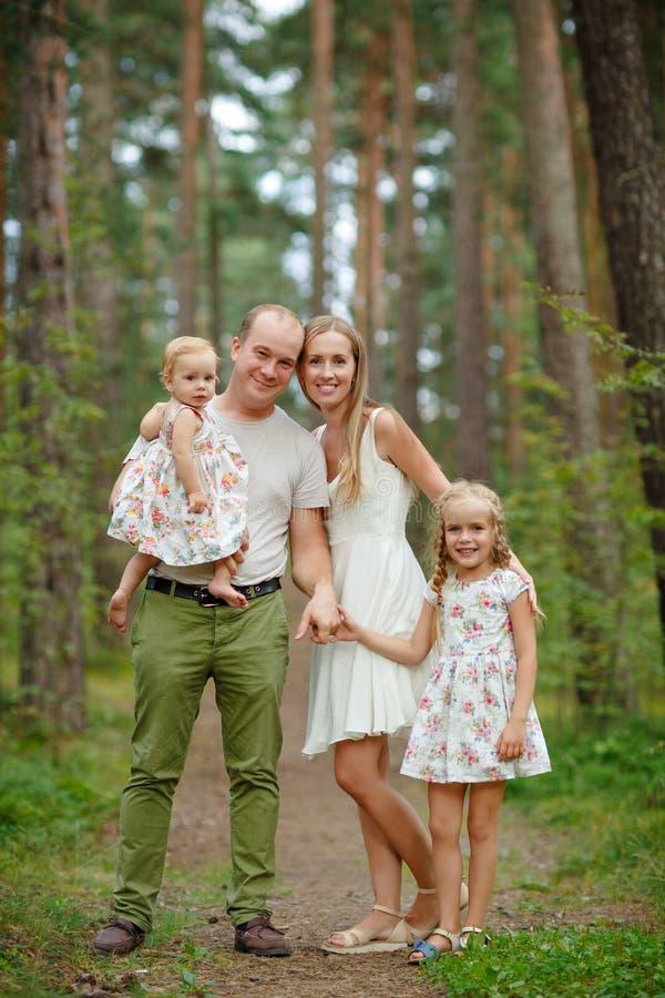 Familia - el caminar rubio de la madre, del padre y de dos hijas a través foto de archivo