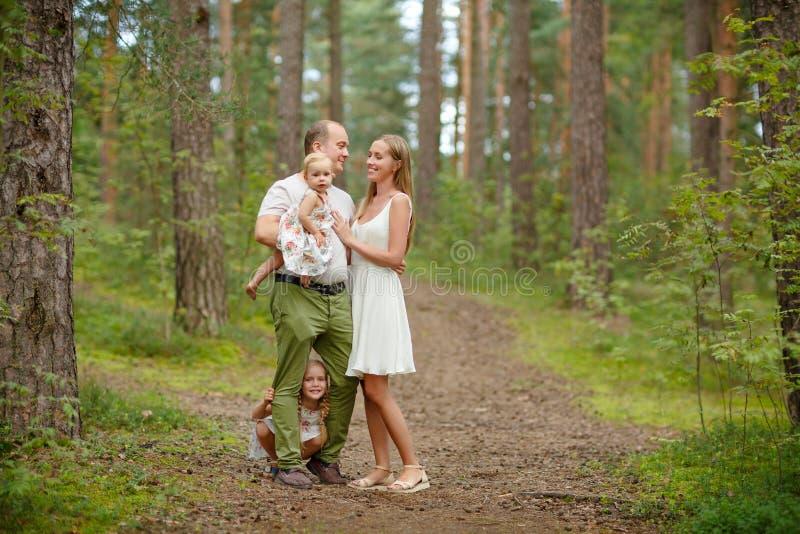 Familia - el caminar rubio de la madre, del padre y de dos hijas a través fotografía de archivo