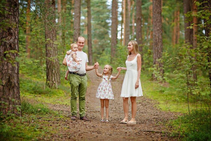 Familia - el caminar rubio de la madre, del padre y de dos hijas a través fotos de archivo