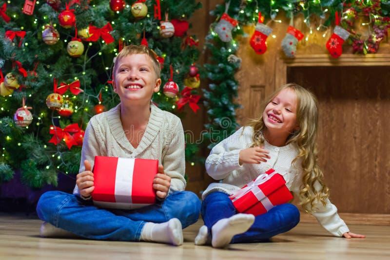 Familia el Nochebuena en la chimenea Niños que abren presentes de Navidad imagen de archivo