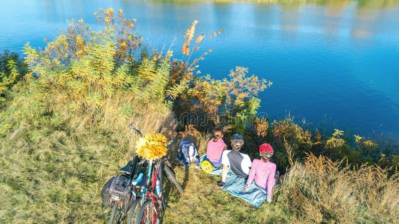 Familia el otoño de las bicis que completa un ciclo al aire libre, padres y niño activos en las bicicletas, opinión aérea la fami fotos de archivo