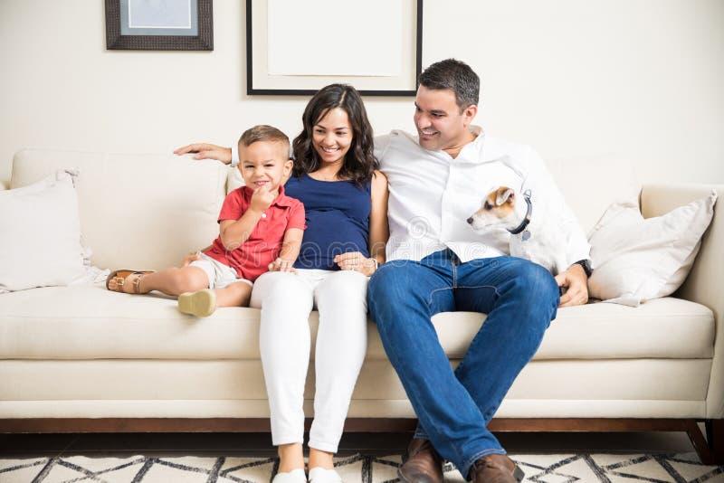 Familia embarazada feliz con tiempo de la calidad del gasto del perro en casa imagen de archivo
