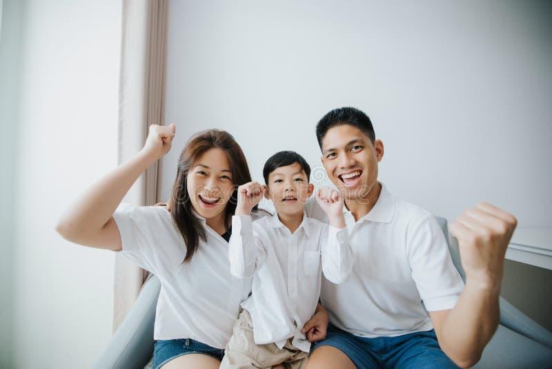 Familia emocionada y feliz con los brazos aumentados mientras que mira televis fotografía de archivo libre de regalías