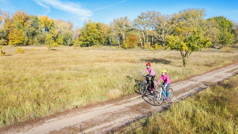 Familia en aire libre de ciclo del otoño de las bicis, madre activa y niño en las bicicletas, opinión aérea la familia feliz con  foto de archivo libre de regalías