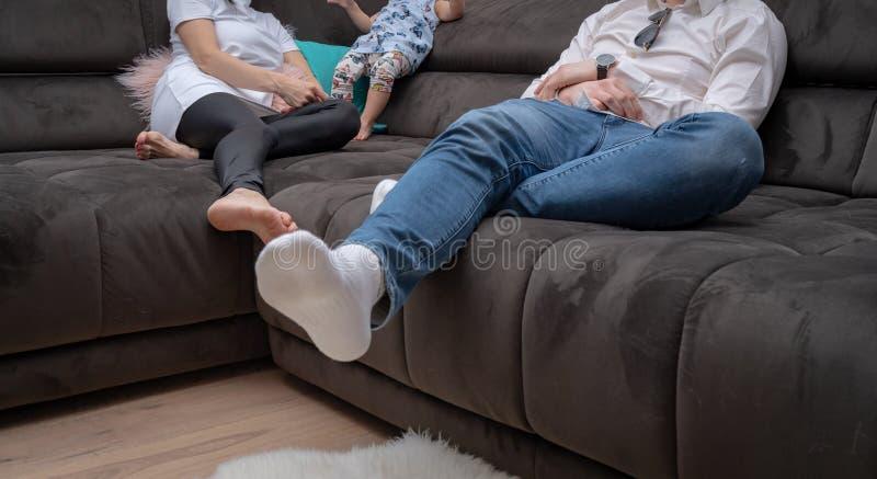 Familia en casa en el sofá imagenes de archivo