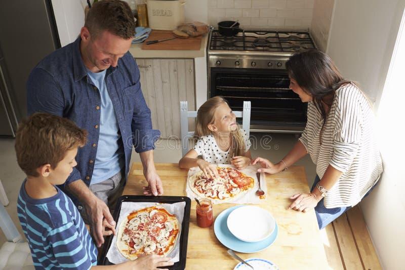 Familia en casa en la cocina que hace las pizzas juntas foto de archivo libre de regalías
