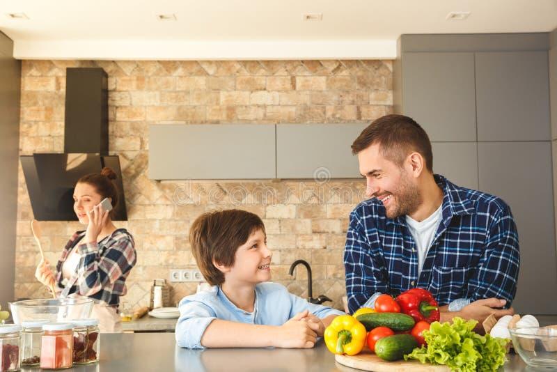 Familia en casa en la situación del padre y del hijo de la cocina junto que mira uno a alegre mientras que llamada de contestació imagenes de archivo