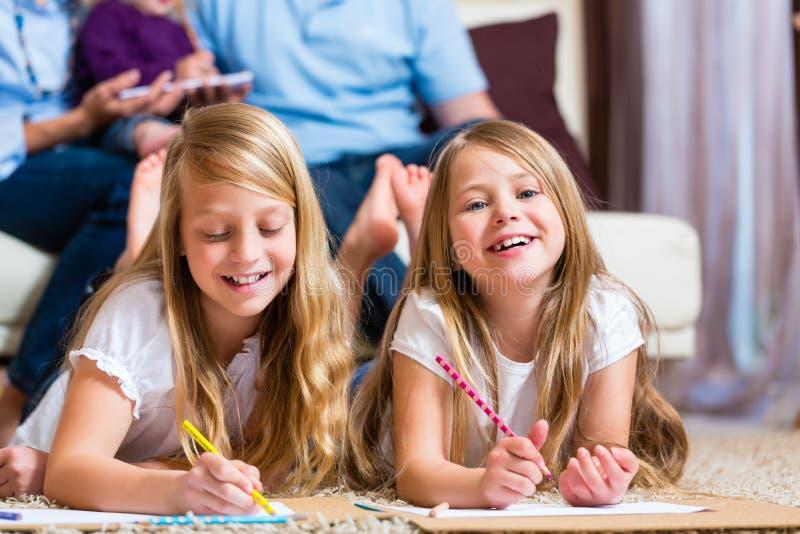 Familia en casa, los niños que colorean en suelo imagen de archivo libre de regalías