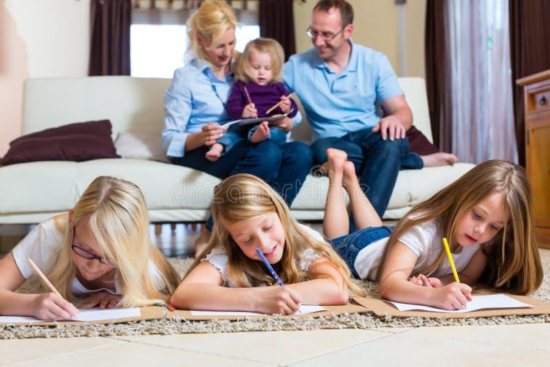 Familia en casa, los niños que colorean en suelo fotografía de archivo libre de regalías