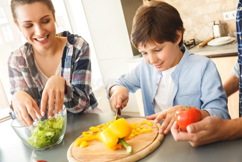 Familia en casa que se coloca en la cocina que hace al hijo de la ensalada junto que corta verduras primer emocionado sonriente c imagenes de archivo