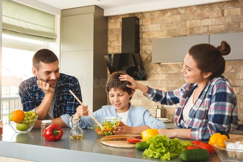 Familia en casa que se inclina en la tabla en los padres de la cocina junto que miran la sonrisa de mezcla de la ensalada del hij imágenes de archivo libres de regalías