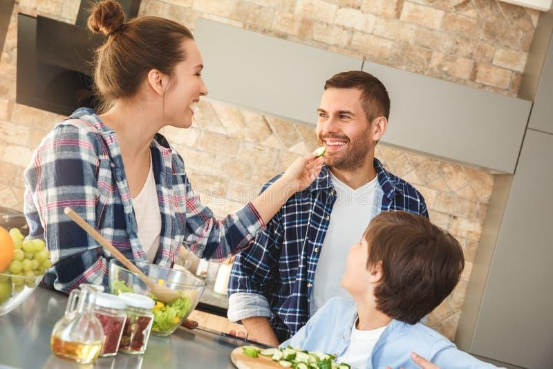 Familia en casa que se une en la esposa de la cocina que da el pedazo del marido de pepino alegre imagen de archivo