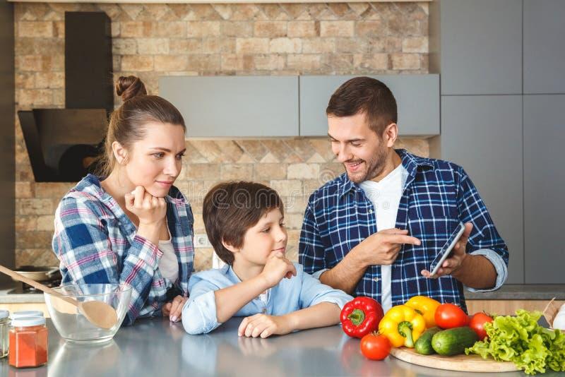 Familia en casa que se une en la madre y el hijo de la cocina que miran concentrados el vídeo de la demostración del padre en dig foto de archivo