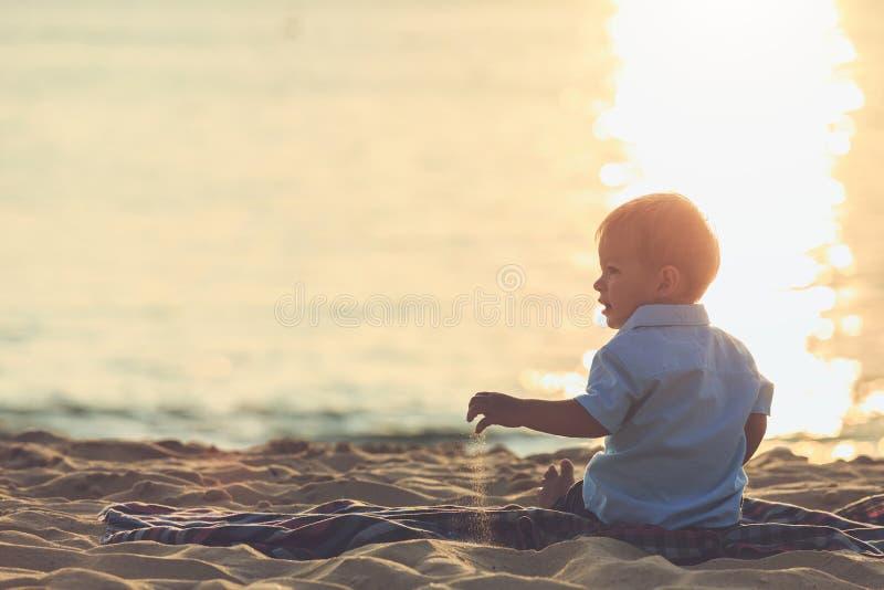 Familia en el concepto de la playa, muchacho caucásico que localiza y que sostiene el sa foto de archivo libre de regalías