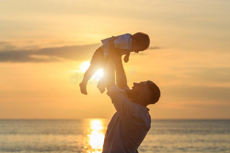 Familia en el concepto de la playa, padre que juega y que lleva a su hijo foto de archivo