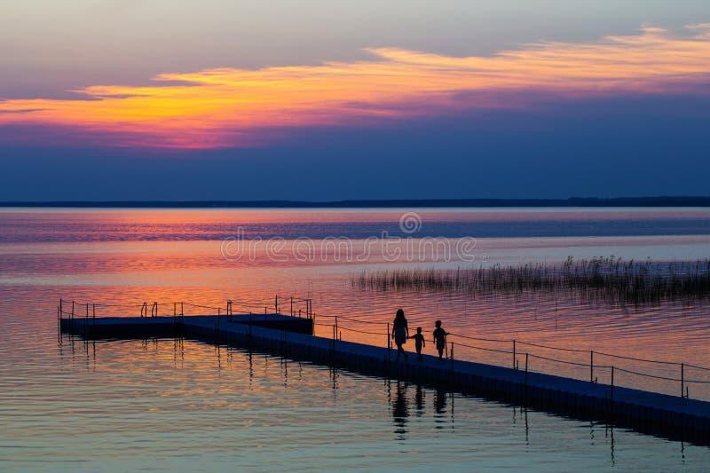 Familia en el embarcadero el pontón en la puesta del sol fotografía de archivo libre de regalías