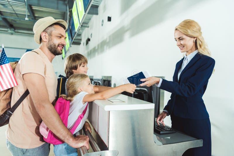 Familia en el escritorio del incorporar en el aeropuerto imagenes de archivo