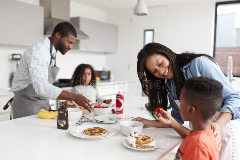 Familia en la cocina en casa que hace las crepes juntas imagen de archivo libre de regalías