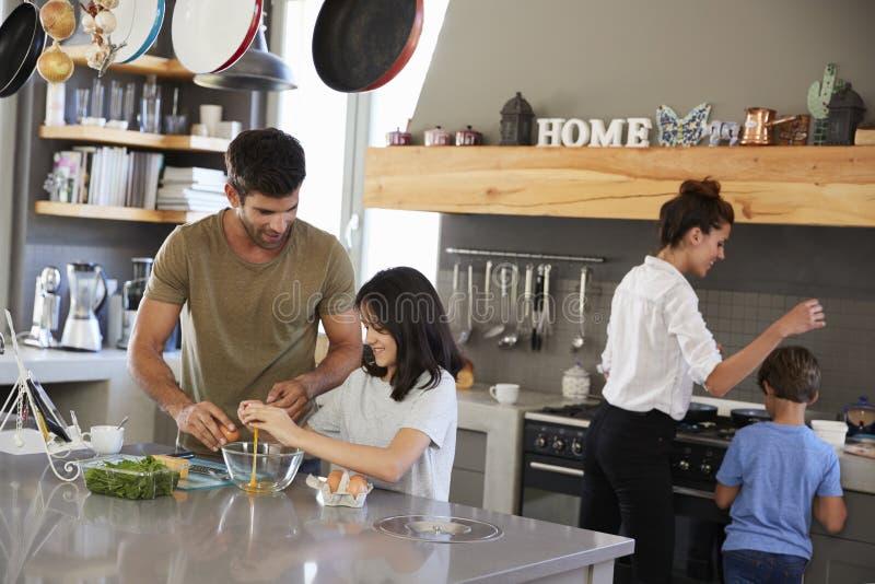 Familia en la cocina que hace el desayuno de la mañana junto imagenes de archivo